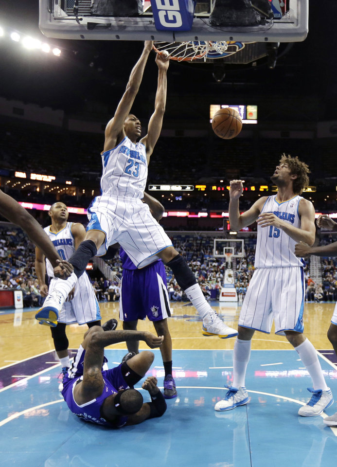 New Orleans Hornets power forward Anthony Davis (23) dunks over Sacramento Kings center DeMarcus Cousins, on the court, during the first half of an NBA basketball game in New Orleans, Sunday, Feb. 24, 2013. At right is Hornets center Robin Lopez (15). (AP Photo/Gerald Herbert)