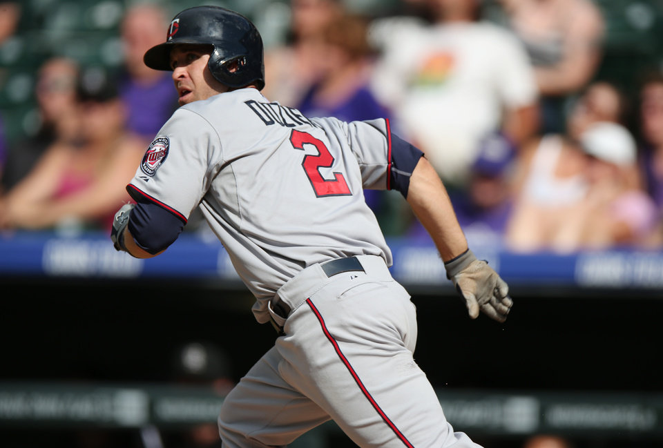 Photo - Minnesota Twins' Brian Dozier follows the flight of his solo home run to lead off the eighth inning against the Colorado Rockies in the Twins' 13-5 victory in an interleague baseball game in Denver on Sunday, July 13, 2014. Dozier followed up with a three-run home run in the ninth inning to hit two home runs in the game. (AP Photo/David Zalubowski)