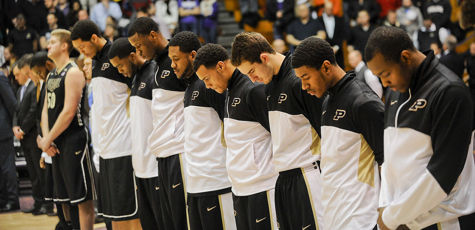 Photo - Members of the Purdue mens basketball team pause for a moment of silence before their NCAA college basketball game against Northwestern in Evanston, Ill., on Tuesday, Jan. 21, 2014. Their was shooting on their campus earlier in the day. (AP Photo/Matt Marton)