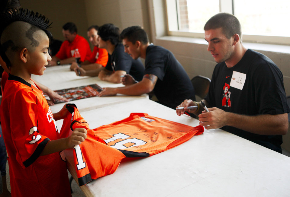J.W. Walsh, right, signs the jersey of Dominik Villanueva, 9 of Oklahoma City, left, at fan appreciation day at Gallagher-Iba Arena in Stillwater on August 3, 2013. KT King, For The Oklahoman