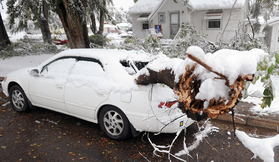 A huge branch sticks out from a broken out back window of a car parked  in Greeley, Colo.  after it fell during the heavy wet snow on Wednesday, Oct. 26, 2011.   Up to 4 inches fell in Denver by Wednesday morning, with more falling in areas to the north. Downed power lines due to snow caused power outages, including one that shut down the University of Northern Colorado in Greeley.  (AP Photo/The Greeley Tribune, Jim Rydbom) ORG XMIT: COGRE101