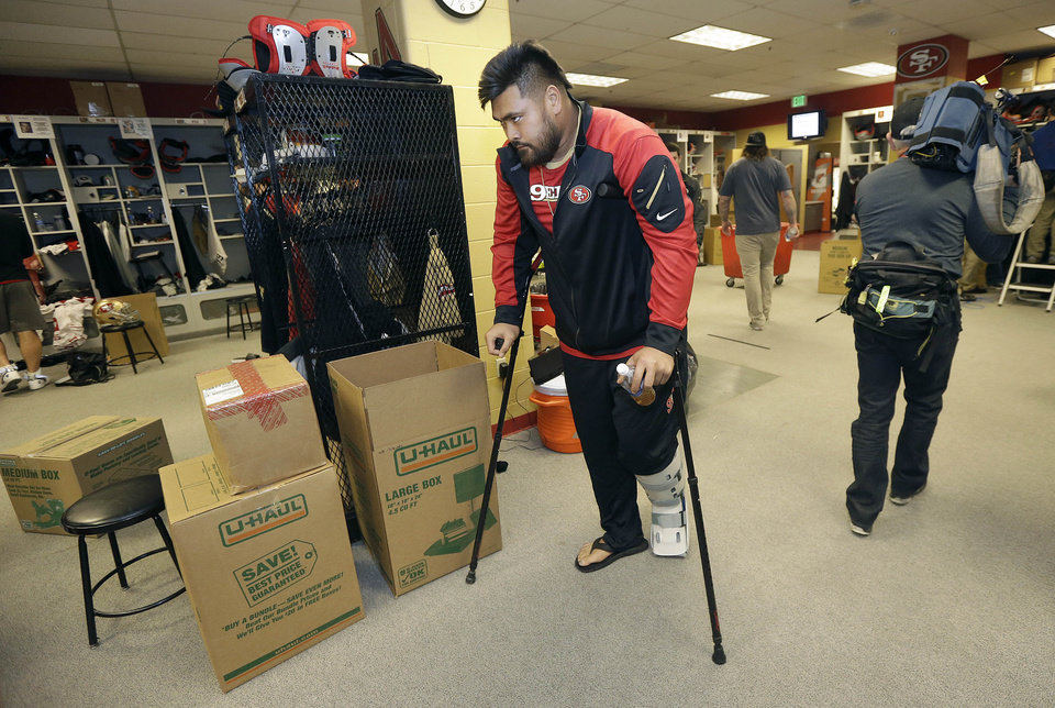 Photo - San Francisco 49ers guard Mike Iupati walks on crutches in the locker room at an NFL training facility in Santa Clara, Calif., Monday, Jan. 20, 2014. The 49ers lost to the Seattle Seahawks in the NFC Championship Game. (AP Photo/Jeff Chiu)