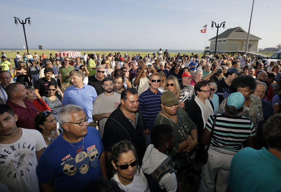 Photo - A large crowd gathers on The Boardwalk at the entrance of the closing Showboat Casino Hotel at four-in-the-afternoon Sunday, Aug. 31, 2014, in Atlantic City, N.J. The Mardi Gras-themed casino is shutting down at 4 p.m. Sunday after 27 years on the Boardwalk. Owner Caesars Entertainment is closing the still-profitable Showboat to reduce the number of casinos in Atlantic City, which has been struggling with plunging revenue and increased competition. (AP Photo/Mel Evans)