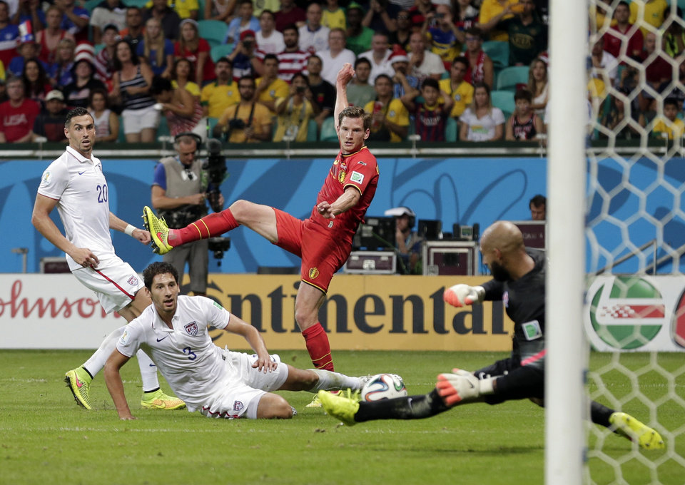 Photo - United States' Omar Gonzalez (3) and Geoff Cameron (20) watch as goalkeeper Tim Howard makes a save on Belgium's Jan Vertonghen shot on goal during the World Cup round of 16 soccer match between Belgium and the USA at the Arena Fonte Nova in Salvador, Brazil, Tuesday, July 1, 2014. (AP Photo/Marcio Jose Sanchez)