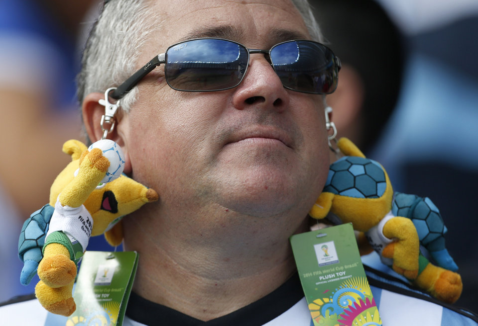 Photo - An Argentine supporter has stuffed-toy World Cup mascots attached to his sunglasses before the group F World Cup soccer match between Nigeria and Argentina at the Estadio Beira-Rio in Porto Alegre, Brazil, Wednesday, June 25, 2014. (AP Photo/Jon Super)