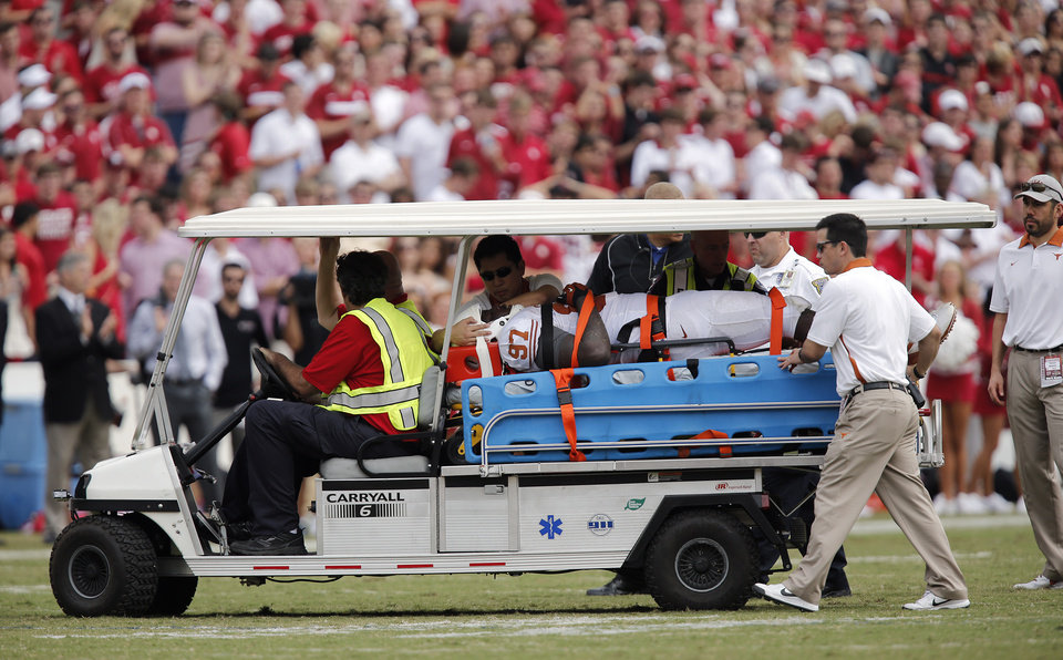 Photo - UT's Brandon Moore (97) is carted off the field with an injury during the Red River Rivalry college football game between the University of Oklahoma (OU) and the University of Texas (UT) at the Cotton Bowl in Dallas, Saturday, Oct. 13, 2012. Photo by Chris Landsberger, The Oklahoman
