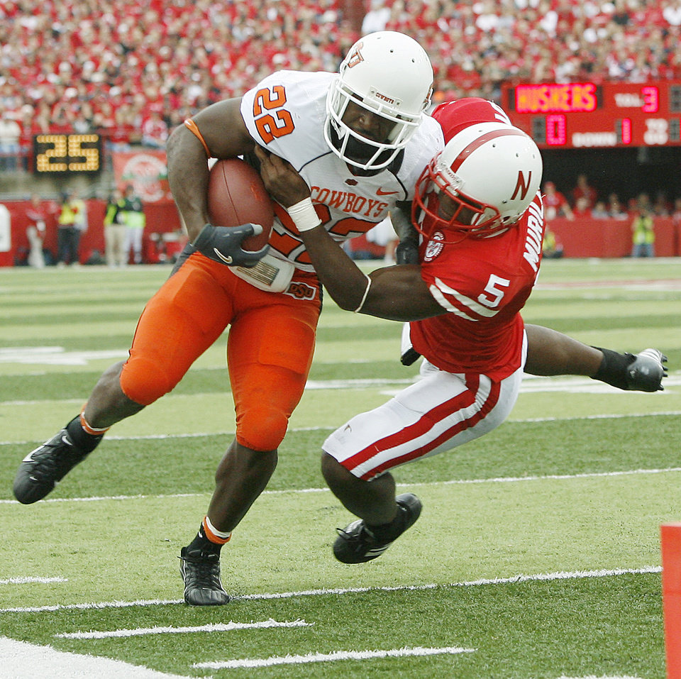 Photo - Dantrell Savage of OSU tries to get past Armando Murillo of Nebraska during  the college football game between Oklahoma State University (OSU) and the University of Nebraska at Memorial Stadium in Lincoln, Neb., on Saturday, Oct. 13, 2007. By Bryan Terry, The Oklahoman