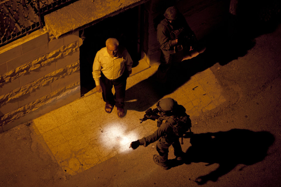 Photo - Israeli soldiers arrest Abdel Aziz Dweik, speaker of the long-defunct Palestinian parliament and a senior Hamas figure, at his home during a military operation to search for three missing Israeli teenagers, in the West Bank city of Hebron, Monday, June 16, 2014. Israel continued its sweep of arrests in the West Bank early Monday, rounding up senior Hamas figures and other Palestinians in a feverish search for three missing Israeli teenagers who Israel says Hamas kidnapped, as Israel's government considered punitive actions against the militant Palestinian group. (AP Photo/Majdi Mohammed)