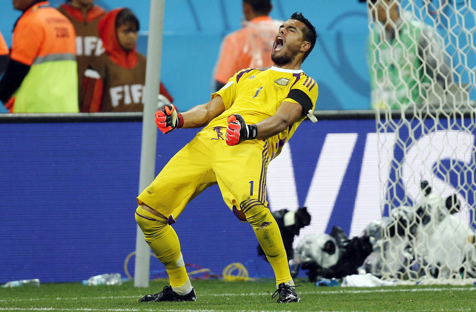 Photo - Argentina's goalkeeper Sergio Romero celebrates after he saved shot by Netherlands' Wesley Sneijder from the spot during the World Cup semifinal soccer match between the Netherlands and Argentina at the Itaquerao Stadium in Sao Paulo, Brazil, Wednesday, July 9, 2014. Argentina beat the Netherlands 4-2 in a penalty shootout to reach the World Cup final. (AP Photo/Frank Augstein)