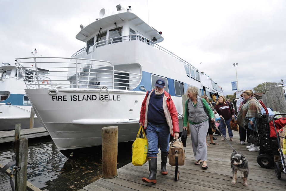 Photo -   Passengers depart one of the last ferries from the Fire Island communities in preparation for the arrival of Hurricane Sandy, Sunday, Oct., 28, 2012, in Bay Shore, N.Y. (AP Photo/Kathy Kmonicek)