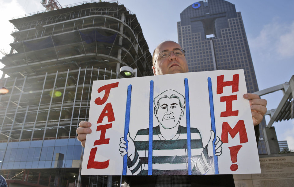 Photo -  Dan Sullivan holds a sign of protest outside the annual ExxonMobil shareholders meeting Wednesday in Dallas. AP Photo   LM Otero -  AP