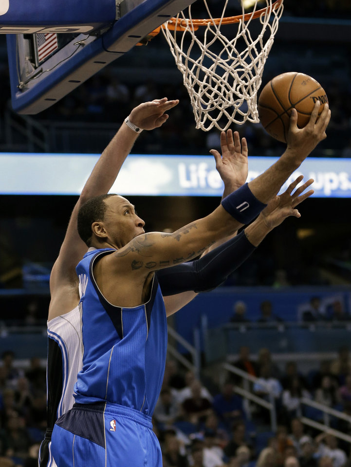 Dallas Mavericks' Shawn Marion, front, makes a shot past Orlando Magic's Josh McRoberts, back left, during the first half of an NBA basketball game, Sunday, Jan. 20, 2013, in Orlando, Fla. (AP Photo/John Raoux)