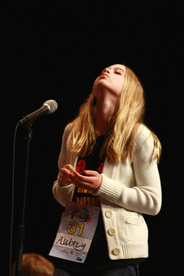Aubrey Snider, eighth-grader from Glencoe concentrates in one of the final rounds of the spelling bee. Aubrey was one of four students standing after 17 rounds.  <strong>by Lynette Lobban, For The Oklahoman</strong>