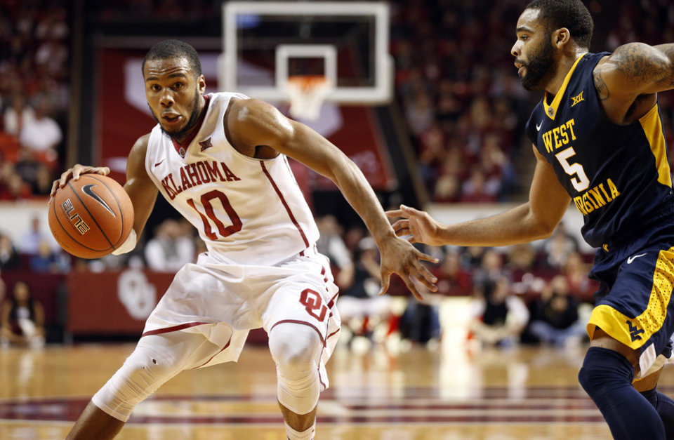 Photo - Oklahoma's Jordan Woodard (10) drives around West Virginia's Jaysean Paige (5) as the University of Oklahoma Sooner (OU) men play the West Virginia Mountaineers (WV) in NCAA, college basketball at The Lloyd Noble Center on Jan. 16, 2016 in Norman, Okla. Photo by Steve Sisney, The Oklahoman