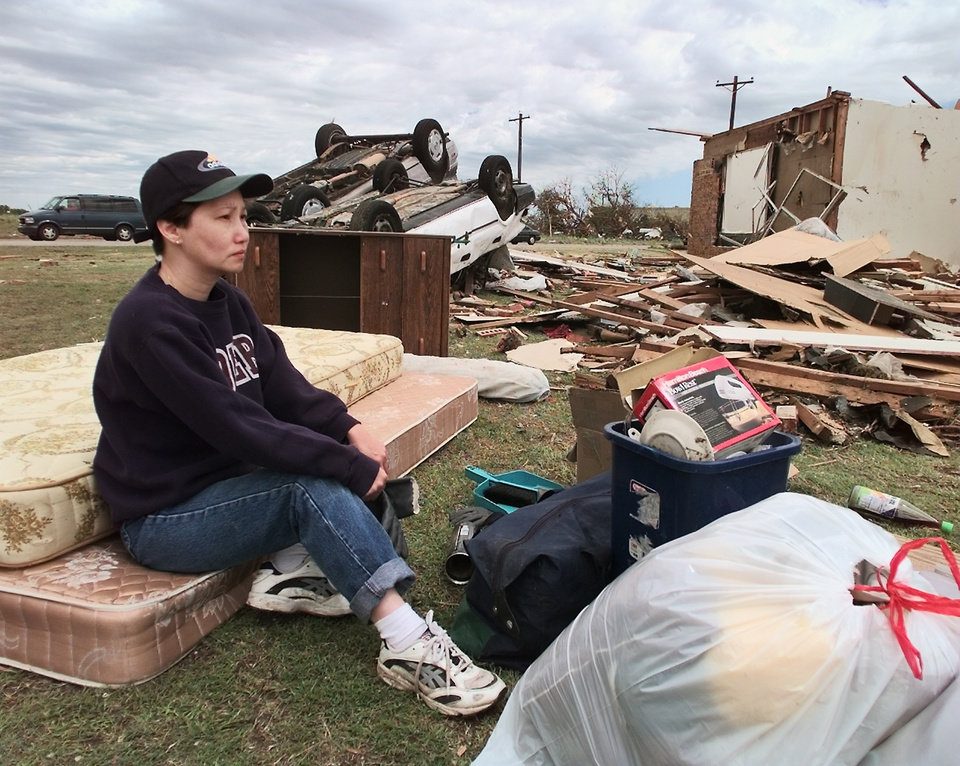 MAY 3, 1999 TORNADO: Dung Mai sits on her mattresses, her two cars are upside down behind her and her home  demolished  during Monday nights tornado in Moore is on the left.