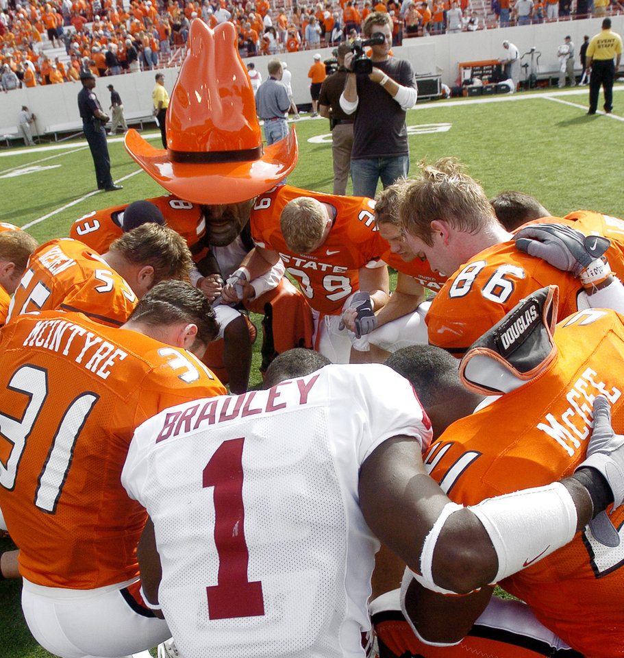 Oklahoma's Mark Bradley (1) joins Oklahoma State Cowboys players and OSU mascot Pistol Pete in prayer after the OU-OSU Bedlam college football game Saturday, October 30, 2004 at Boone Pickens Stadium in Stillwater, Okla.  OU defeated OSU 38-35. Bradley scored on three touchdown passes from Jason White. By Ty Russell/The Oklahoman