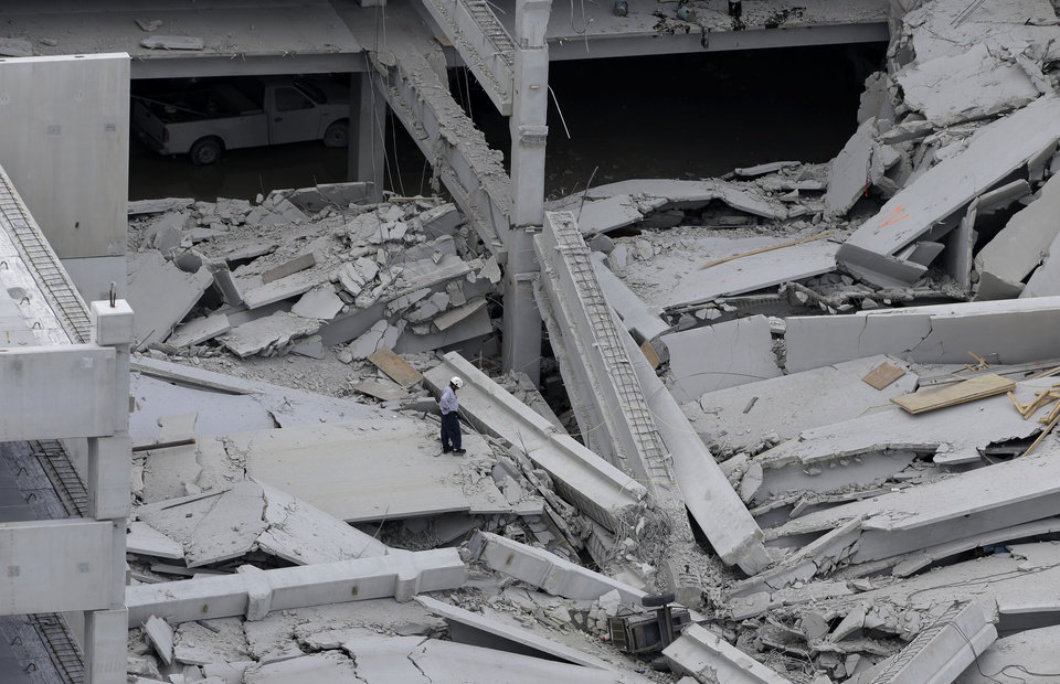Photo -   A rescue worker walks through the rubble at a five-story parking garage after it collapsed at Miami-Dade College, Wednesday, Oct. 10, 2012 in Miami, killing one worker and trapping two others in the rubble, officials said. Several other workers were hurt, including one rescued from the debris. (AP Photo/Lynne Sladky)
