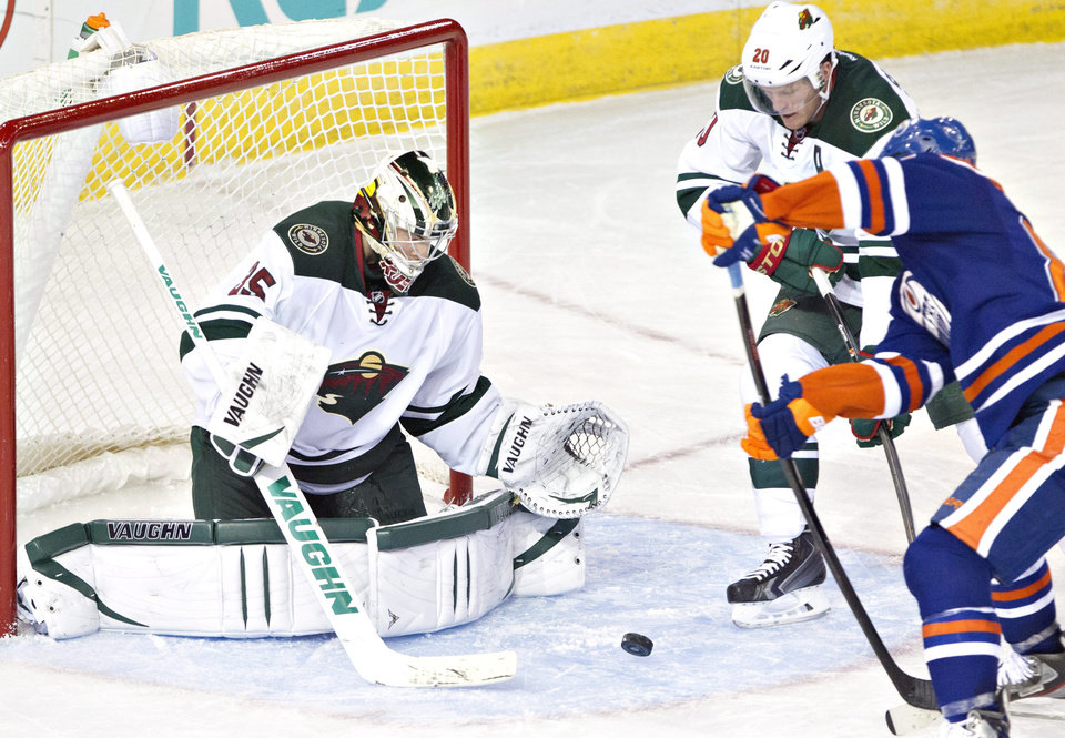 Photo - Minnesota Wild's goalie Darcy Kuemper (35) makes the save on Edmonton Oilers' Sam Gagner (89) as Ryan Suter (20) tries to defend during third period NHL hockey action in Edmonton,  Alberta, on Thursday Feb. 27, 2014. (AP Photo/The Canadian Press, Jason Franson)