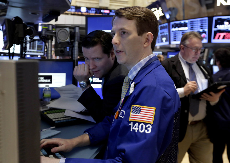 Specialists Gregg Maloney, left, and Peter Elkins, center, work on the floor of the New York Stock Exchange Tuesday, Jan. 22, 2013. Stocks are wavering in early trading on Wall Street as U.S. companies turn in a mixed batch of earnings reports. (AP Photo/Richard Drew)