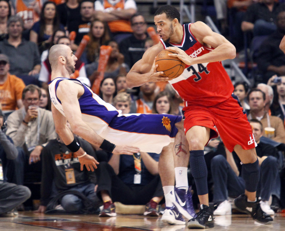 FILE - In this Feb. 20, 2012, file photo, Phoenix Suns center Marcin Gortat, left, of Poland, falls backward to the floor as Washington Wizards center JaVale McGee, right, is called for a charge in the third quarter of an NBA basketball game in Phoenix. The NBA will penalize flopping this season, fining players for repeated violations of an act a league vice president says has