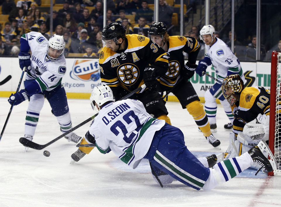 Photo - Vancouver Canucks left wing Daniel Sedin (22) passes the puck to teammate Alex Burrows (14) in front of Boston Bruins goalie Tuukka Rask (40), as Bruins' Patrice Bergeron (37) and Dougie Hamilton (27) defend during the first period of an NHL hockey game in Boston on Tuesday, Feb. 4, 2014. (AP Photo/Elise Amendola)