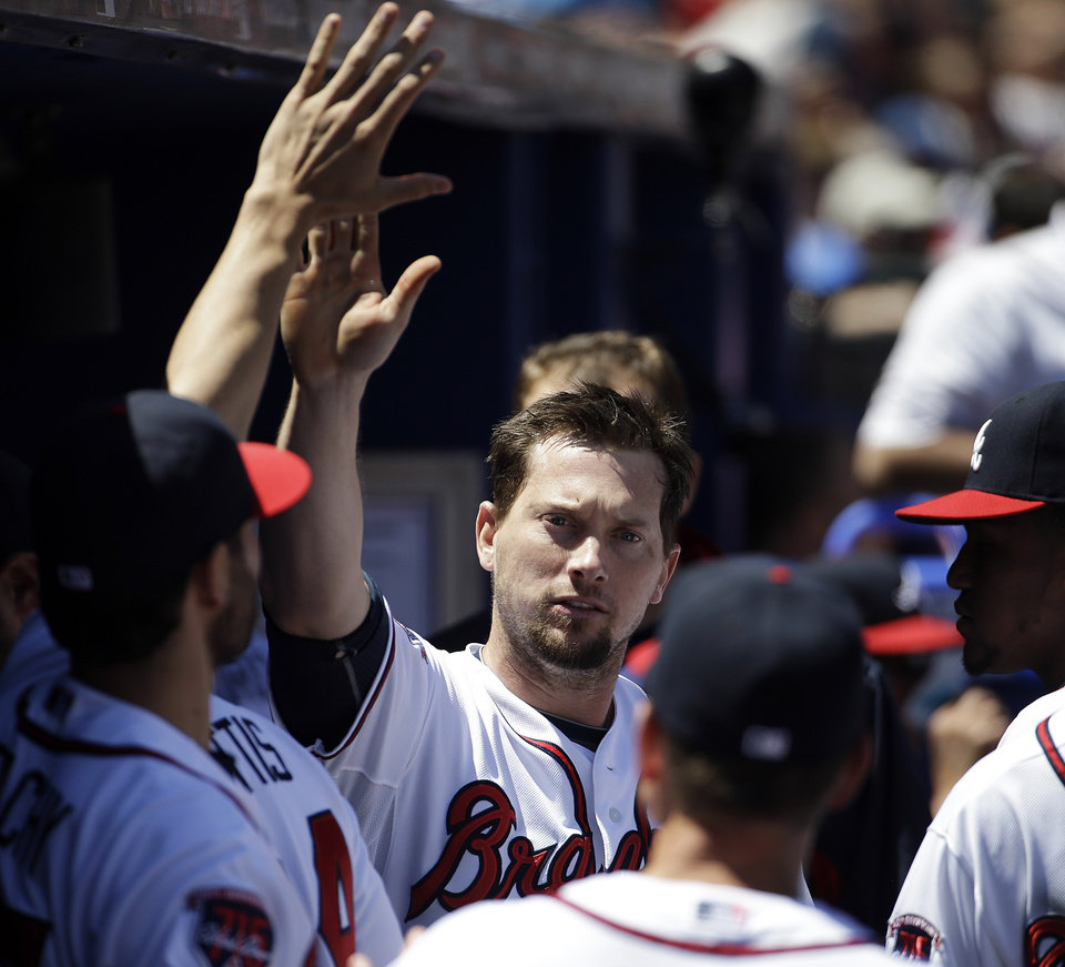 Photo - Atlanta Braves' Chris Johnson, center, high-fives teammates after scoring off a single by Ryan Doumit in the fourth inning of a baseball game against the Miami Marlins, Wednesday, April 23, 2014, in Atlanta. (AP Photo/David Goldman)
