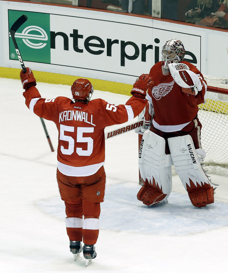 Photo - Detroit Red Wings defenseman Niklas Kronwall (55), of Sweden, celebrates with goalie Jimmy Howard (35) after defeating the Chicago Blackhawks 2-0 in Game 4 of the Western Conference semifinals in the NHL hockey Stanley Cup playoffs in Detroit, Thursday, May 23, 2013. (AP Photo/Paul Sancya)