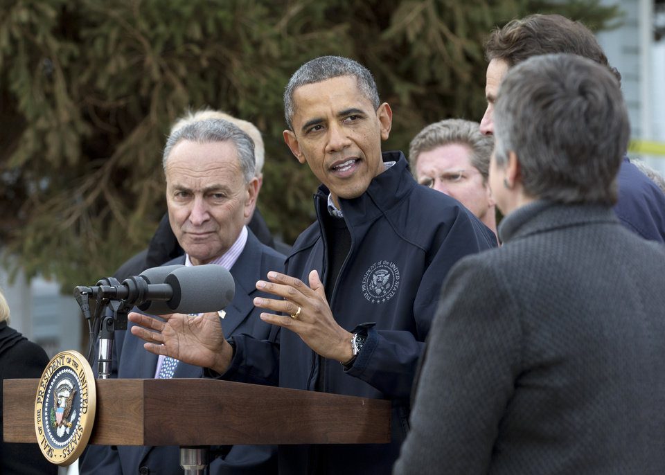 Photo -   President Barack Obama gestures as he speaks during a news conference on Cedar Grove Avenue, a street significantly impacted by Superstorm Sandy, Thursday, Nov. 15,2012, on Staten Island, in New York. From left are, Sen. Charles Schumer, D-N.Y., the president, Housing and Urban Development Secretary Shaun Donovan, New York Gov. Andrew Cuomo and Homeland Security Secretary Janet Napolitano. (AP Photo/Carolyn Kaster)