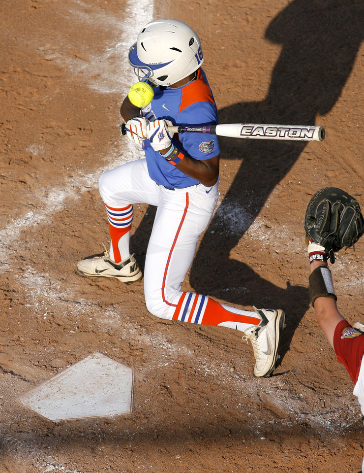 Photo - Florida's Michelle Moultrie (16) is hit during the Women's College World Series game between Florida and Alabama at the ASA Hall of Fame Stadium in Oklahoma City, Sunday, June 5, 2011. Photo by Garett Fisbeck, The Oklahoman