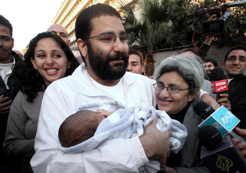 Photo - FILE - In this Sunday, Dec. 25, 2011 file photo, Egyptian prominent blogger Alaa Abdel Fattah, center, hugs his recently born son, Khaled, his mother Laila Soueif, and his sister Ahdaf Soueif, left, after his release, in Cairo, Egypt. Egypt's Islamist president makes good on vows of action against opponents, as the top prosecutor issues arrest warrants against five prominent activists and summons opposition politicians for questioning over weekend clashes between the Muslim Brotherhood and protesters. (AP Photo/ Amr Hafez, File)