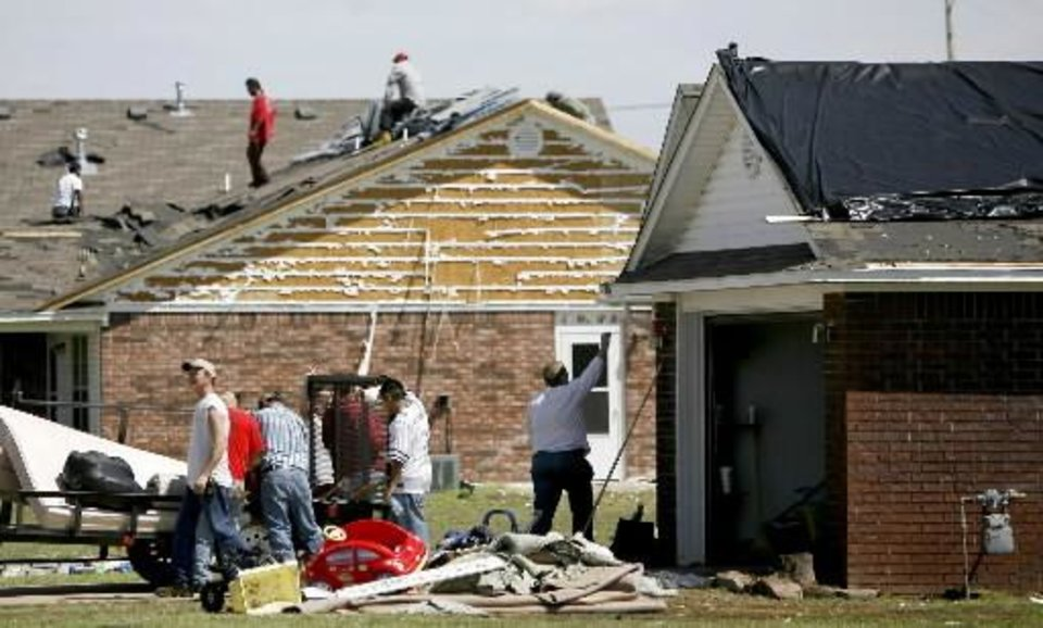 Residents work to clean up damage in Muldrow, Okla., home, Thursday, April 10, 2008, after severe storms moved through the area Wednesday. Photo by Bryan Terry