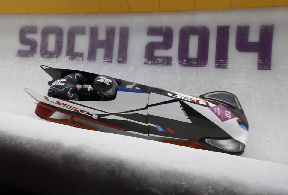 Photo - The team from the United States USA-1, piloted by Steven Holcomb and brakeman Steven Langton, take a curve during the men's two-man bobsled competition at the 2014 Winter Olympics, Sunday, Feb. 16, 2014, in Krasnaya Polyana, Russia. (AP Photo/Natacha Pisarenko)