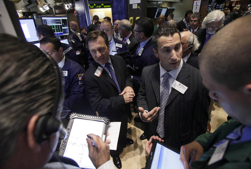 Traders gather at a post on the floor of the New York Stock Exchange during the IPO of Northern Tier Energy, Thursday, July 26, 2012. U.S. stocks soared at the opening bell after the president of the European Central Bank vowed to do what it takes to preserve the continent's monetary union. (AP Photo/Richard Drew)