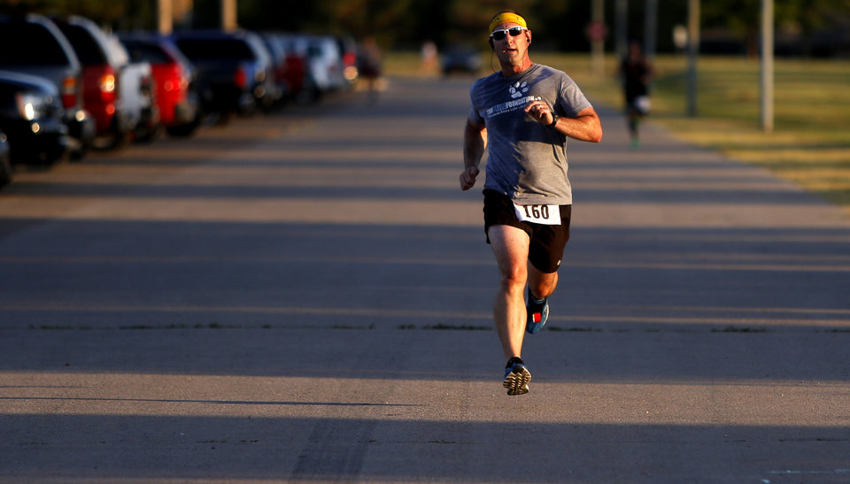 Greg Roberts, of Edmond, finishes a free 5k run in Stars and Stripes Park at Lake Hefner in Oklahoma City on Wednesday, July 18, 2012, to promote the upcoming Rush Springs Watermelon Festival. Photo by Bryan Terry, The Oklahoman