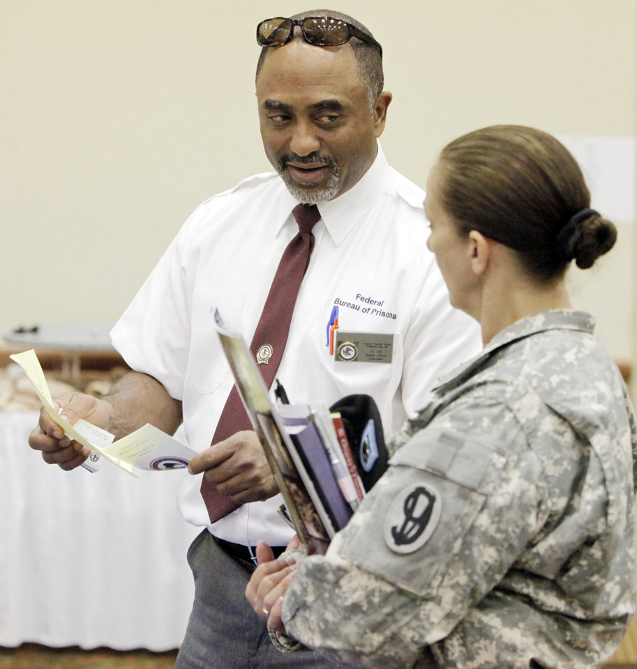 Officer Harold Hill from the Federal Transfer Center talks to Lt. Col. Shirley May of the Army Reserves about careers with the Federal Bureau of Prisons during the Oklahoma Yellow Ribbon Job Fair at the Clarion Meridian Convention Center in Oklahoma City, Friday, May 29, 2009. Photo by Nate Billings, The Oklahoman