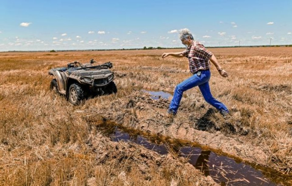 Photo -  David VonTungeln jumps across a wide rut while checking his wheat crop in a soggy and rain-saturated field. [JIM BECKEL/THE OKLAHOMAN]