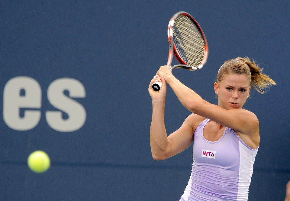 Photo - Camila Giorgi, of Italy, hits a backhand during her 6-2, 6-4 semifinal loss to Magdalena Rybarikova, of Slovakia, at the New Haven Open tennis tournament in New Haven, Conn., on Friday, Aug. 22, 2014. (AP Photo/Fred Beckham)