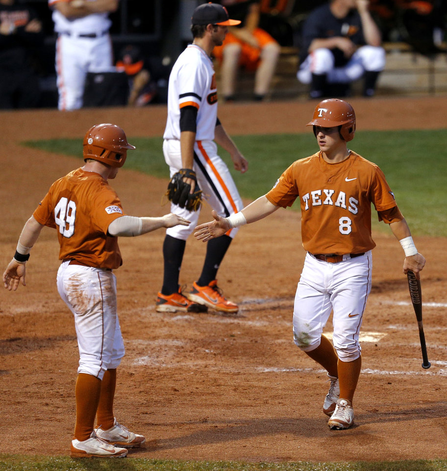 Photo - Texas' Brooks  Marlow, right, celebrates a run with Zane Gurwitz as OSU's Garrett Williams in the fourth inning of a Big 12 Tournament baseball game between Oklahoma State University and the University of Texas at Chickasaw Bricktown Ballpark in Oklahoma City, Saturday, May 24, 2014. Photo by Bryan Terry The Oklahoman