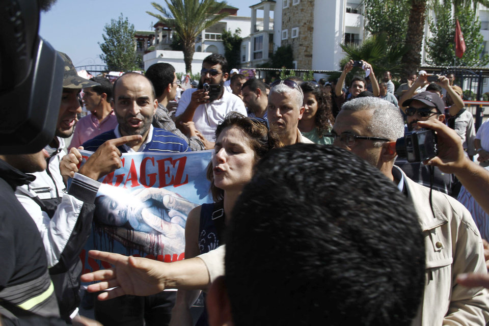Photo -   Anti-abortion protesters mob Rebecca Gomperts, centre, the Dutch founder of Women on Waves, an abortion advocacy group, on Oct. 4, 2012 in the port of Smir, Morocco . Moroccan authorities sealed off the port where a Dutch abortion ship was set to arrive at , while demonstrators protested against its arrival in the Mediterranean port town where Gomperts was waiting to greet it. Abortion is illegal in most cases in Morocco and it also is forbidden to give out information about such procedures. (AP/Paul Schemm).