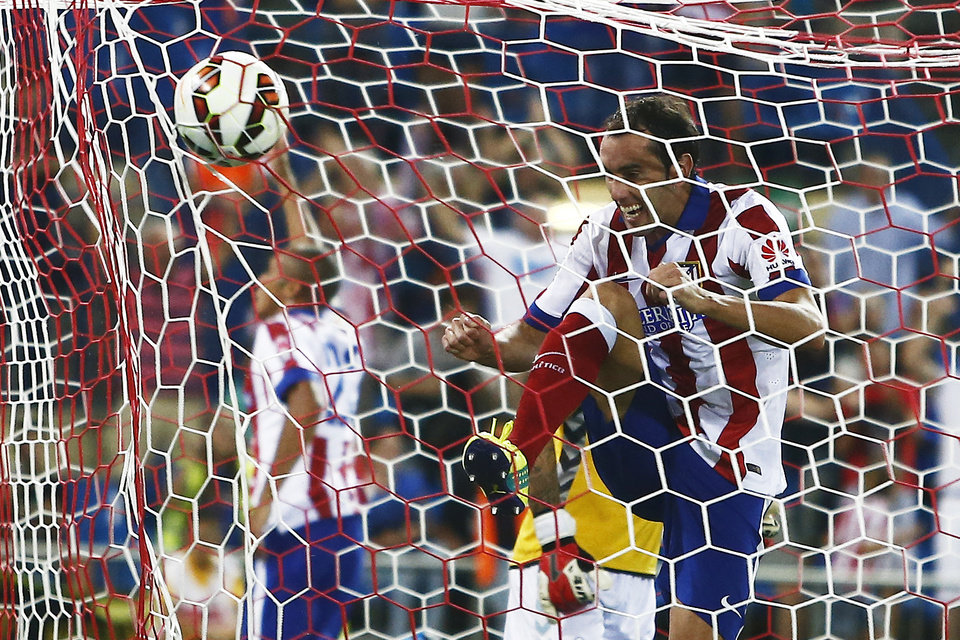 Photo - Atletico's Diego Godin, from Uruguay celebrates Joao Miranda's goal during a Spanish La Liga soccer match between Atletico de Madrid and Eibar at the Vicente Calderon stadium in Madrid, Spain, Saturday, Aug. 30, 2014. (AP Photo/Andres Kudacki)