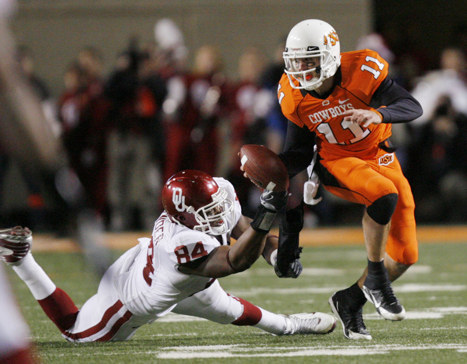 Photo - OSU quarterback Zac Robinson barely escapes OU's Frank Alexander during the first half of the college football game between the University of Oklahoma Sooners (OU) and Oklahoma State University Cowboys (OSU) at Boone Pickens Stadium on Saturday, Nov. 29, 2008, in Stillwater, Okla. STAFF PHOTO BY CHRIS LANDSBERGER