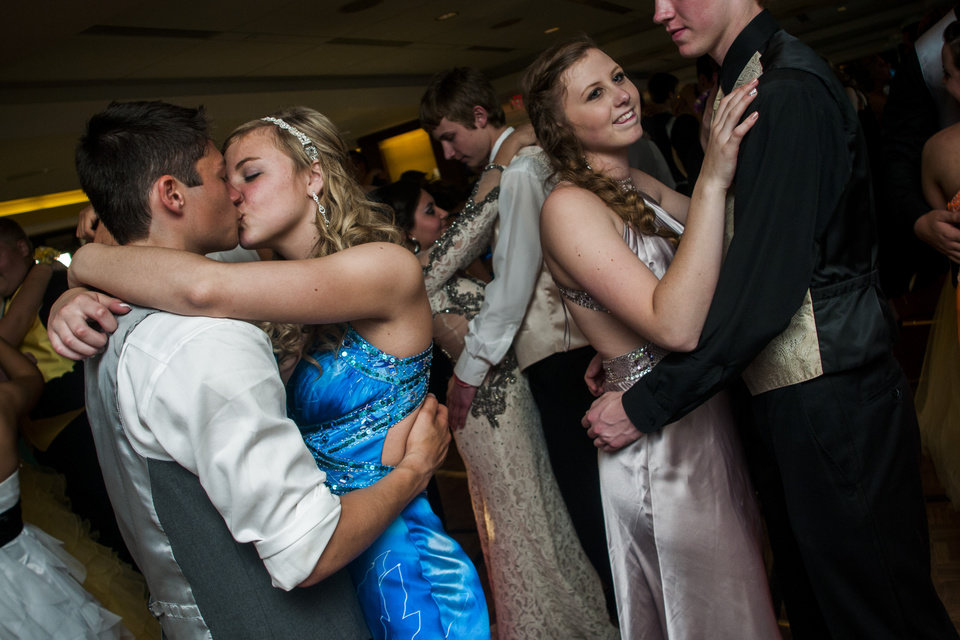 Photo - Durand senior Jarren Guy, left, kisses his girlfriend, Kaylee Jones as the two dance at Michigan Stadium on the University of Michigan campus, Saturday, May 10, 2014, in Ann Arbor, Mich. The junior-senior prom for students at Durand High School was the first prom hosted by the 100,000-plus-seat football venue. The group took photos on the field, visited the locker rooms and had their dancing and dinner in the Jack Roth Stadium Club until midnight. (AP Photo/The Flint Journal, Jake May) LOCAL TV OUT; LOCAL INTERNET OUT