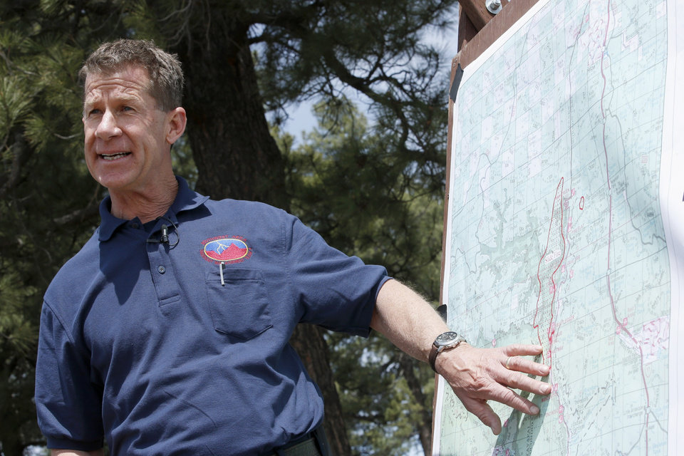 Photo - Bill Morse, the public information officer for the Southwest Area Type 1 Incident Management Team, talks about the Slide Fire burning nearby on Thursday, May 22, 2014, in Kachina Village, Ariz.   The fire, which has burned approximately 4,800 acres, is 3 to 3 1/2 miles away from the residential areas of Forest Highlands and Kachina Village, where the 3,200 residents remain under pre-evacuation warnings. (AP Photo/Ross D. Franklin)