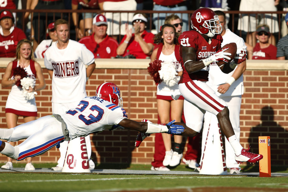 Photo - Oklahoma's Keith Ford (21) scores past Louisiana Tech's Kentrell Brice (23) during a college football game between the University of Oklahoma Sooners (OU) and the Louisiana Tech Bulldogs at Gaylord Family-Oklahoma Memorial Stadium in Norman, Okla., on Saturday, Aug. 30, 2014. Photo by Bryan Terry, The Oklahoman
