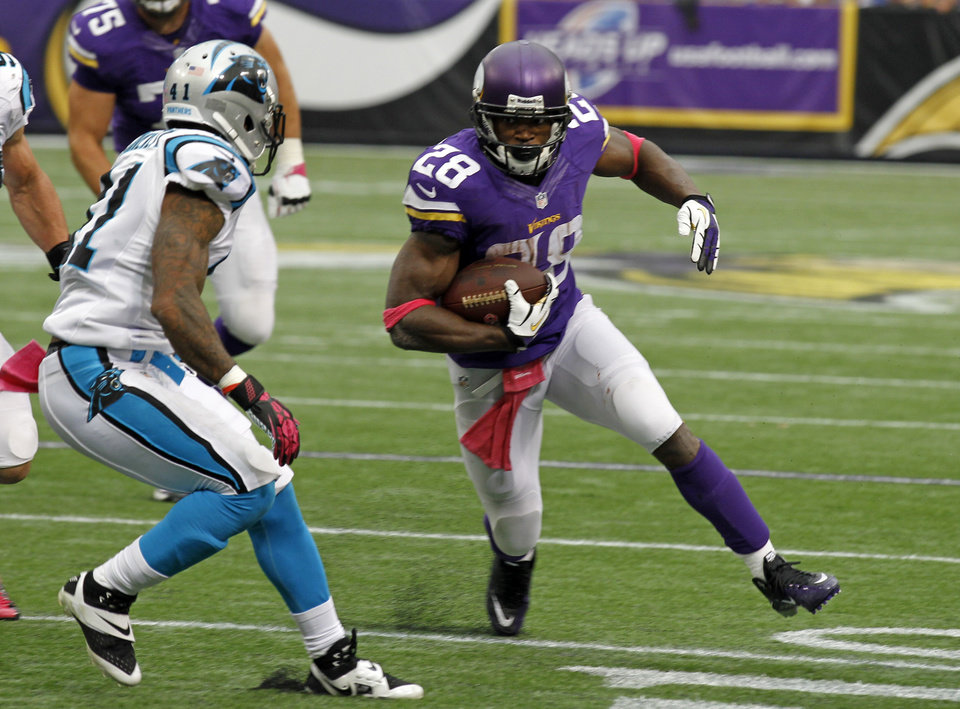 Photo - Carolina Panthers cornerback Captain Munnerlyn, left, chases down Minnesota Vikings running back Adrian Peterson during the first half of an NFL football game in Minneapolis, Sunday, Oct. 13, 2013. (AP Photo/Ann Heisenfelt)