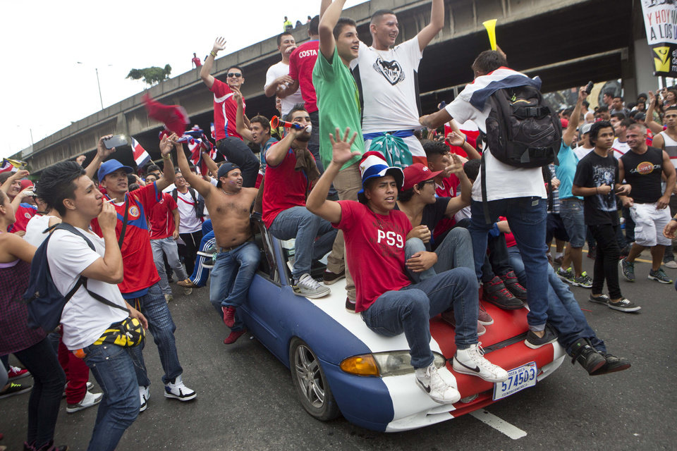 Photo - Costa Rica soccer fans on a car painted in the colors of the nation's flag celebrate their team's victory over Greece at a Brazil World Cup round of 16 game in San Jose, Costa Rica, Sunday, June 29, 2014. Costa Rica won a penalty shootout 5-3 after the match ended 1-1 following extra time. (AP Photo/Esteban Felix)