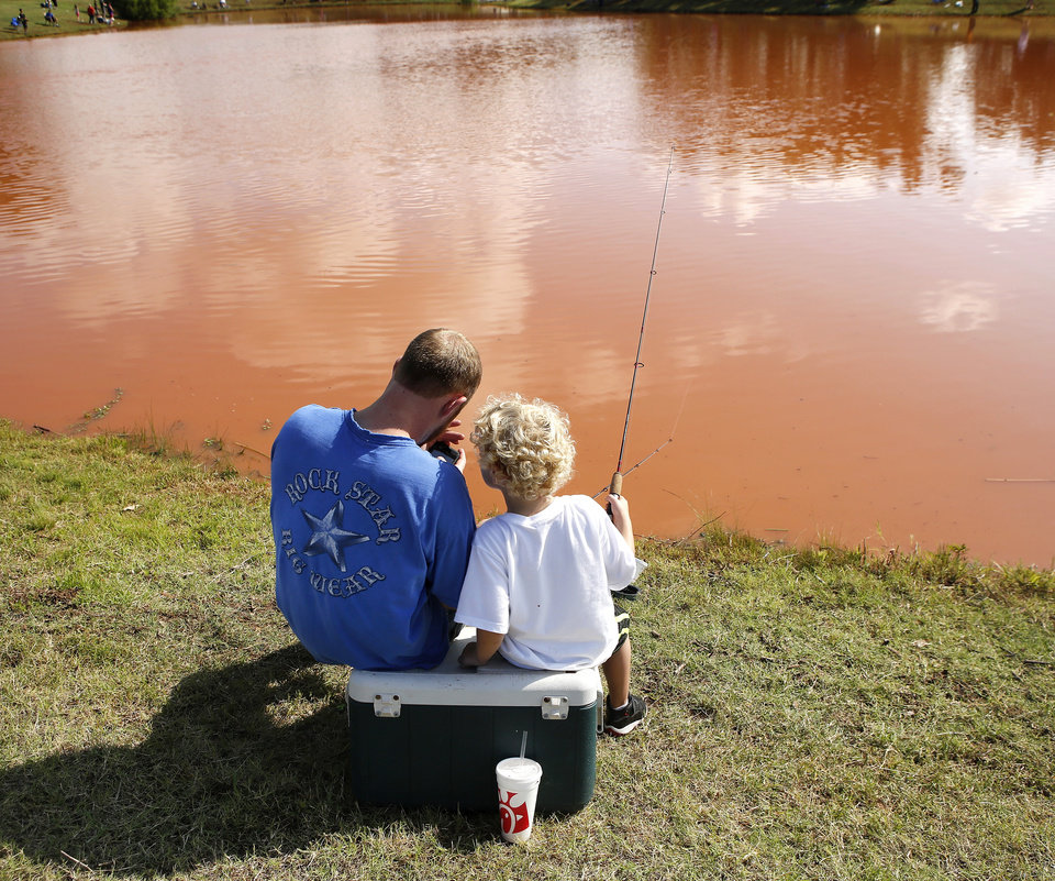 Photo - Corey Hurt and his son, Luke, 5, sit atop their ice chest while they fish in the derby. Corey said he and his son are