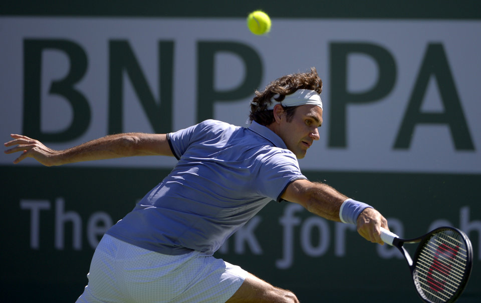 Photo - Roger Federer, of Switzerland, hits to Dmitry Tursunov, of Russia, during a third round match at the BNP Paribas Open tennis tournament, Monday, March 10, 2014, in Indian Wells, Calif. (AP Photo/Mark J. Terrill)