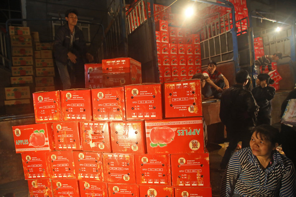 Photo - In this March 9, 2013 photo,  a porter, top, unloads boxes of Chinese red apples at Long Bien wholesale market for fruits and vegetables in Hanoi, Vietnam.  China has emerged as one of the world's leading exporters of fruit and vegetables, and is increasingly taking market share from U.S. producers in Asian markets. It grows more apples than any other country. There are no figures on how much of the crop Vietnam imports. Chinese fruit is often cheaper than Vietnamese, and offers more variety. (AP Photo/Na Son Nguyen)