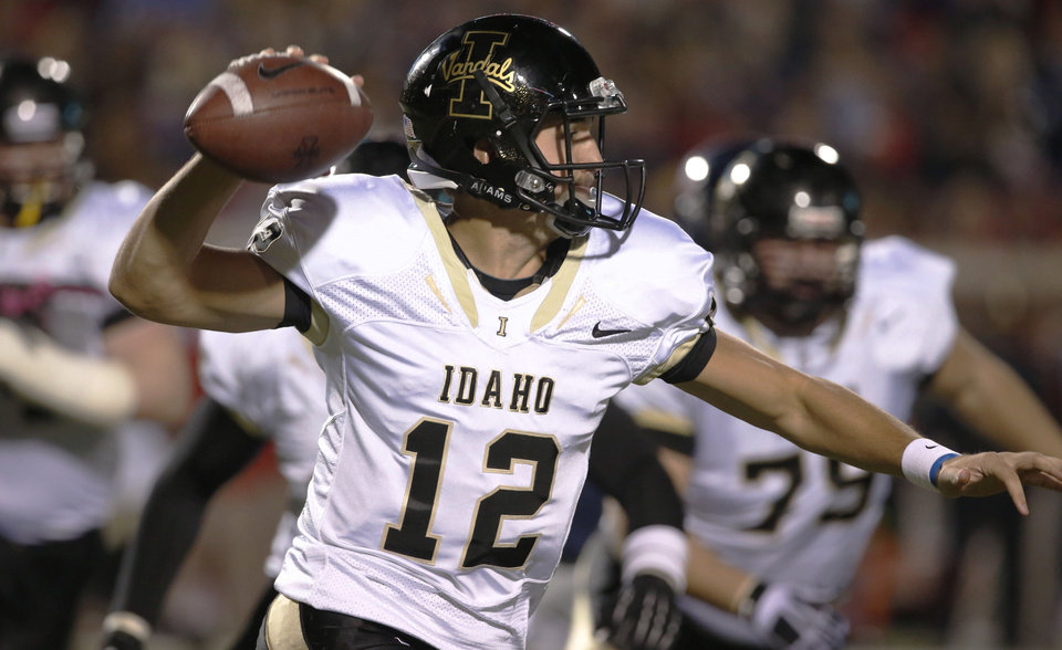 Photo - Idaho quarterback Taylor Davis (12) looks for an open receiver against Mississippi during the first half of their NCAA college football game at Vaught-Hemingway Stadium in Oxford, Miss., on Saturday, Oct. 26, 2013.  (AP Photo/Rogelio V. Solis)